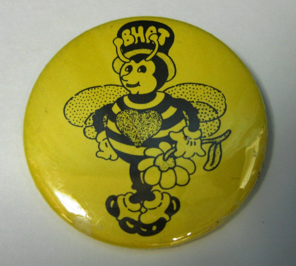 "Yellow pin with illustration of a bee holding a flower and wearing a top-hat with the word ""BHAT"""