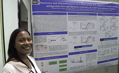 NIH postbac IRTA Chelesa Fearce posing with her poster at Postbac Poster Day