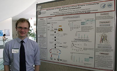 postbac IRTA Ryan Beckner posing with his poster at Postbac Poster Day