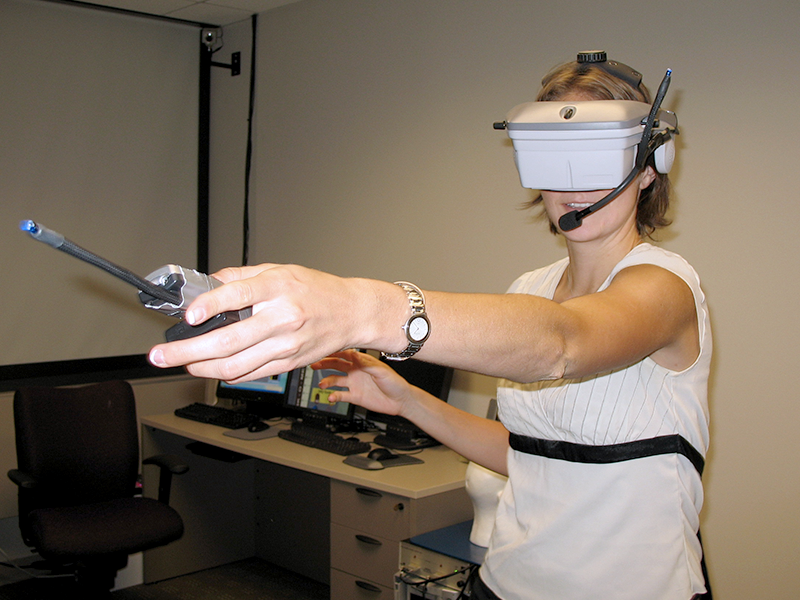 A summer student in the lab of Susan Persky, Ph.D., tests out a virtual reality headset