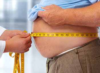 doctor measuring an overweight patient's waist circumference