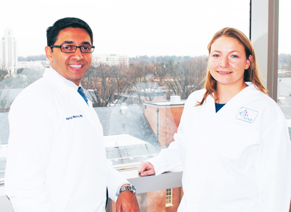man and woman in white coats with window in background overlooking NIH