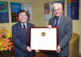 Kuan Teh-Jeang and Michael Gottesman holding a large framed certificate