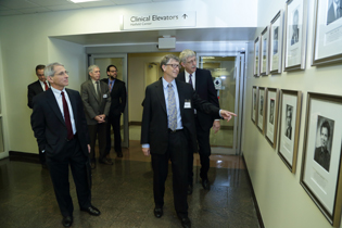 Tony Fauci, Bill Gates, and Francis Collins looking at photos on wall