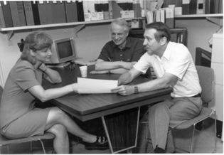 Three people sitting at a table in a conference room.