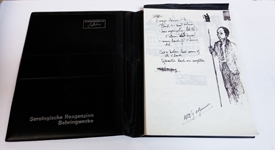 Open notebook with written notes and a sketch of a man