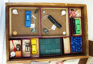 Flat box with compartments with toy cars, blocks, and other items