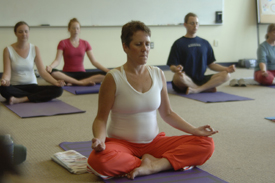 yoga class with people sitting in the lotus position