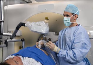 Brad Wood at an imaging machine with patient. Wood is wearing a surgical mask.