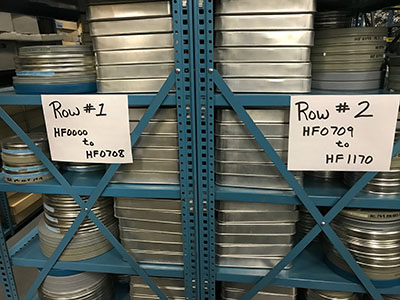 stacks of round metal canisters containing motion picture films