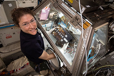 Female astronaut at a scientific workstation aboard the International Space Station