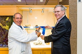 John Gallin and Jeffrey Post cutting the ribbon for the exhibit
