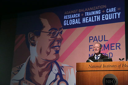 Paul Farmer with a huge illustration of himself on the screen behind him.