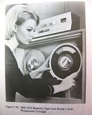 A woman standing in front of a unit containing the old computer tape reels