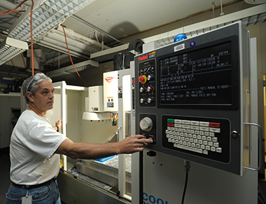 man working at a machine; see caption