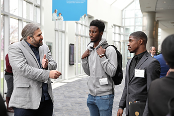Jeremiah Smith chatting with two male students