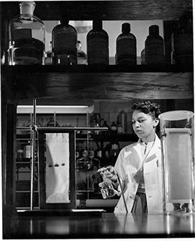 alma levant hayden spraying reagent out of a spray bottle onto vertically held sheet of paper with marks on it.