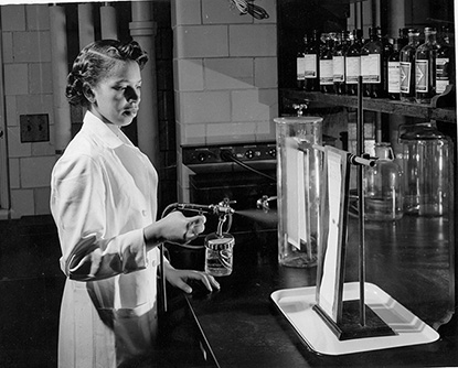 Alma Levant Hayden in the lab spraying paper with a reagent
