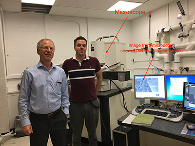 Richard Leapman and Matt Guay standing in front of the powerful microscope.