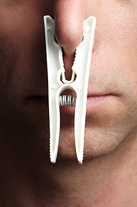 MAN'S NOSE WITH A CLOTHESPIN HOLDING IT SHUT