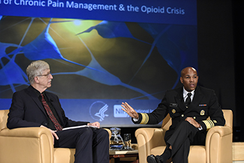 Francis Collins and Jerome Adams sitting on stage at the symposium.
