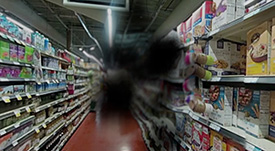 aisle in a grocery store; view is blocked by a black smudge in the middle of the frame.