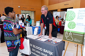 blood bank exhibit with recruiter talking to a woman; green labs fair poster is next to the table