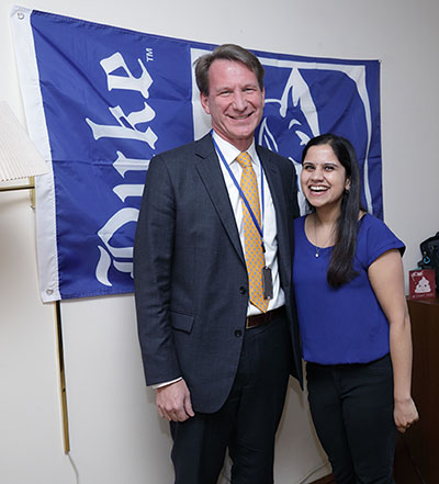 Ned Sharpless and Nicole Dalal in front of Duke banner hanging on wall in Dalal's room.