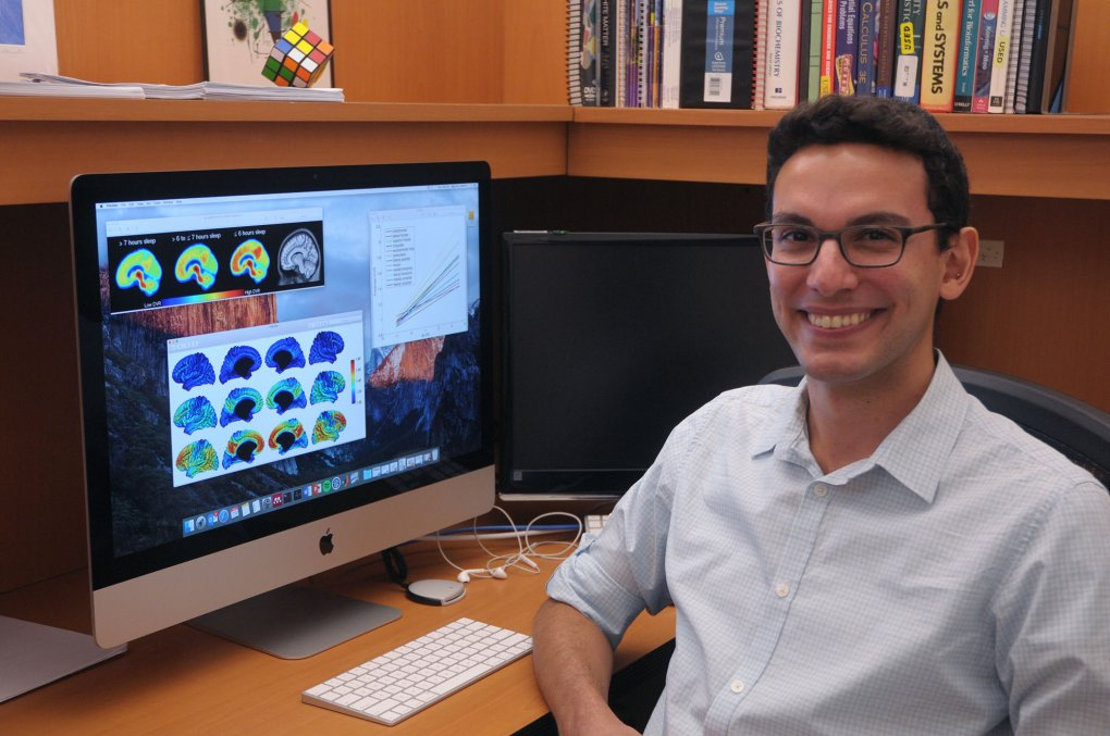 Murat Bilgel, NIH IRP postdoc, at his desk with brain scans