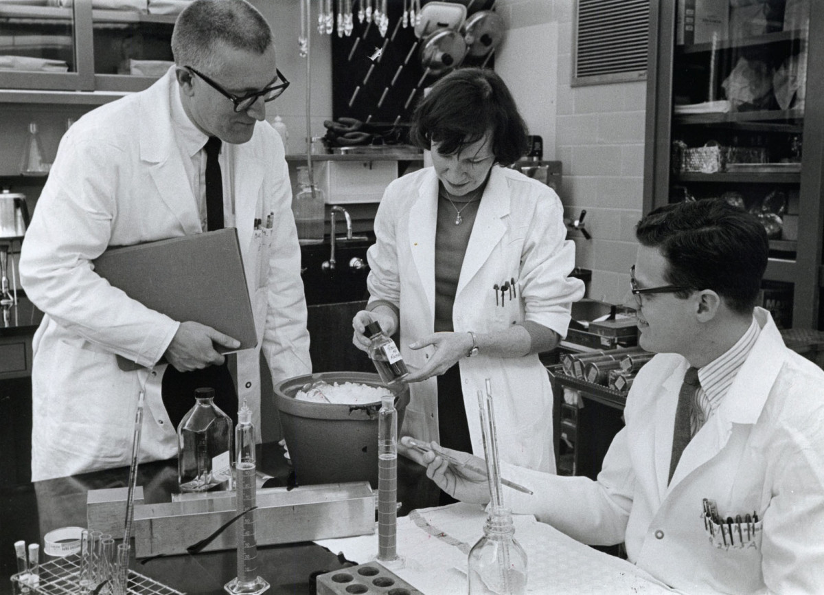 Dr. Meyer (left) and Dr. Parkman (right), along with fellow NIAID scientist Hope Hopps, inspect a culture of the virus that causes rubella