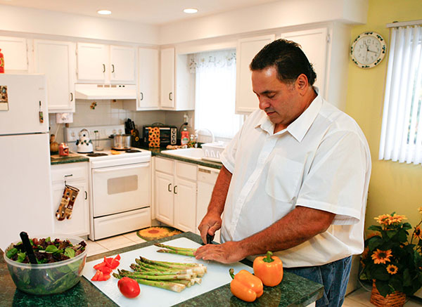 man chopping vegetables in his kitchen