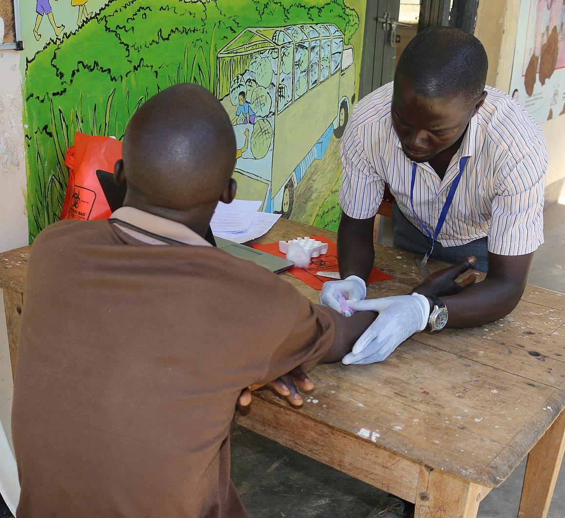 A research assistant draws blood for HIV testing from a participant in the Rakai Community Cohort Study.
