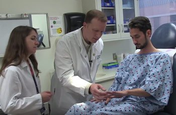 Nancy's son Charlie sits in an exam room discussing his health with dermatologists Dominique Pichard and Edward Cowen.