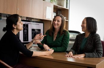 Dr. Sharon Savage meets with other members of her research team in her office.