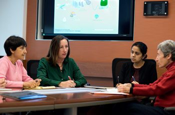 Dr. Sharon Savage talks with her team in a conference room.